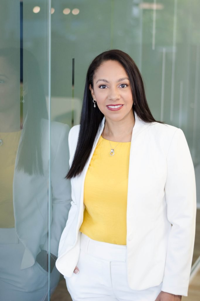 Karina Hilton Marketing Strategy Expert looking straight wearing a white suit and yellow blouse