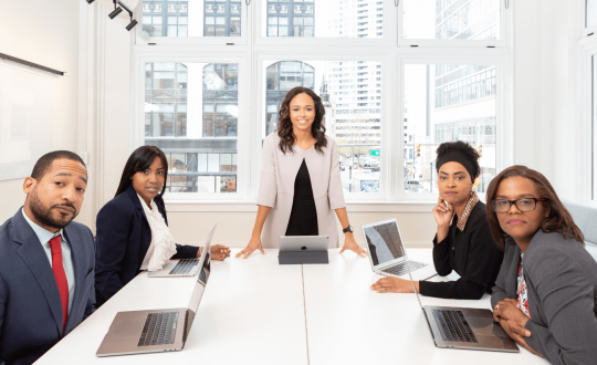 A group of business people sitting around a table looking at a woman standing up looking successful
